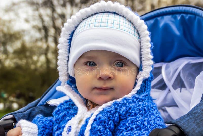 Portret van leuke baby met engelenogen die in wandelwagen zitten De leeftijd van de baby is 6 maanden royalty-vrije stock afbeeldingen