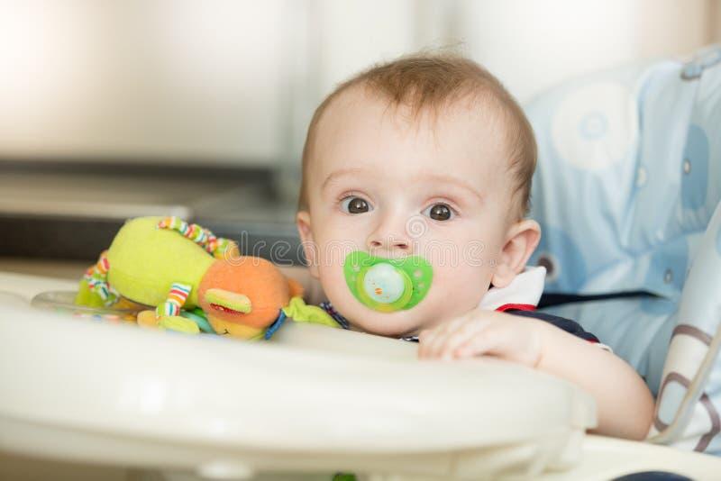 Portret van leuke babyjongen met soother die op ontbijt binnen wachten royalty-vrije stock fotografie