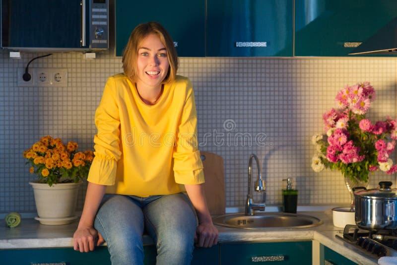 Portret van leuke de vrouwenzitting van Yong op keukencountertops en het leuke glimlachen stock foto's
