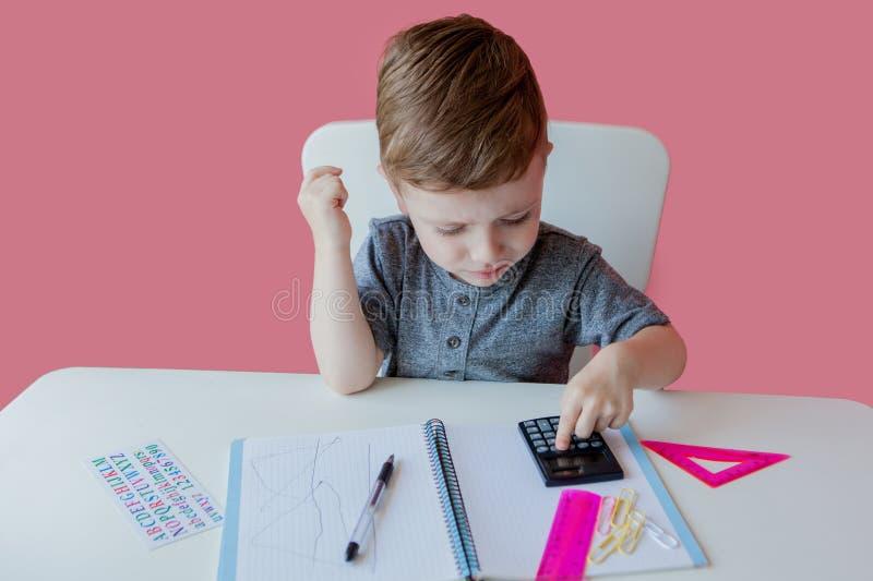 Portret van leuke jong geitjejongen die thuis thuiswerk maken Weinig geconcentreerd kind die met kleurrijk potlood schrijven, bin stock afbeelding