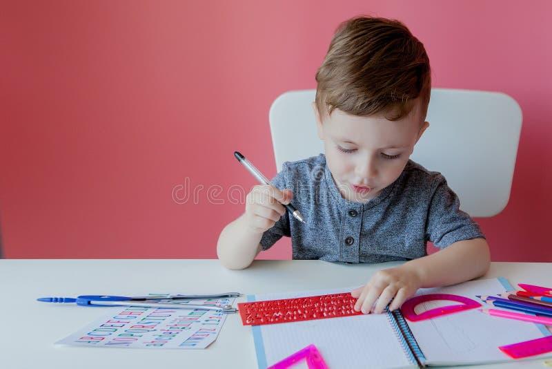 Portret van leuke jong geitjejongen die thuis thuiswerk maken Weinig geconcentreerd kind die met kleurrijk potlood schrijven, bin stock fotografie