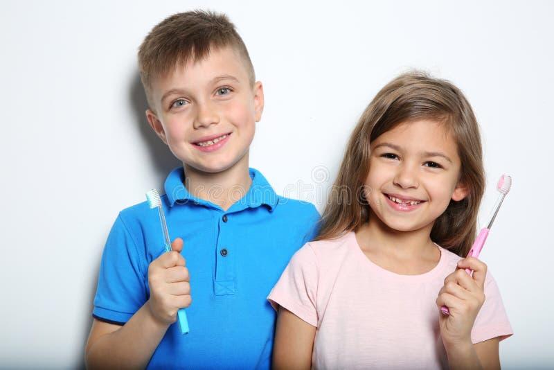 Portret van leuke kinderen met tandenborstels op wit stock afbeelding