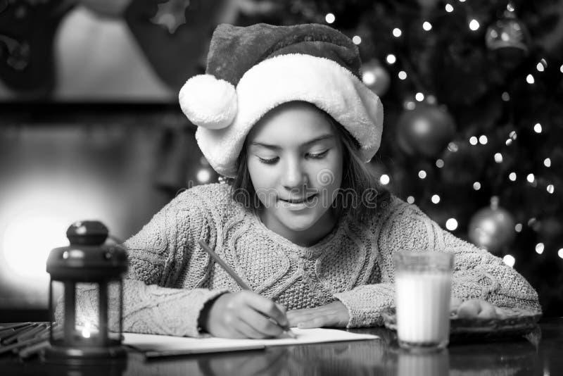 Portret van leuke meisje het schrijven brief aan Santa Claus bij het leven ro stock foto