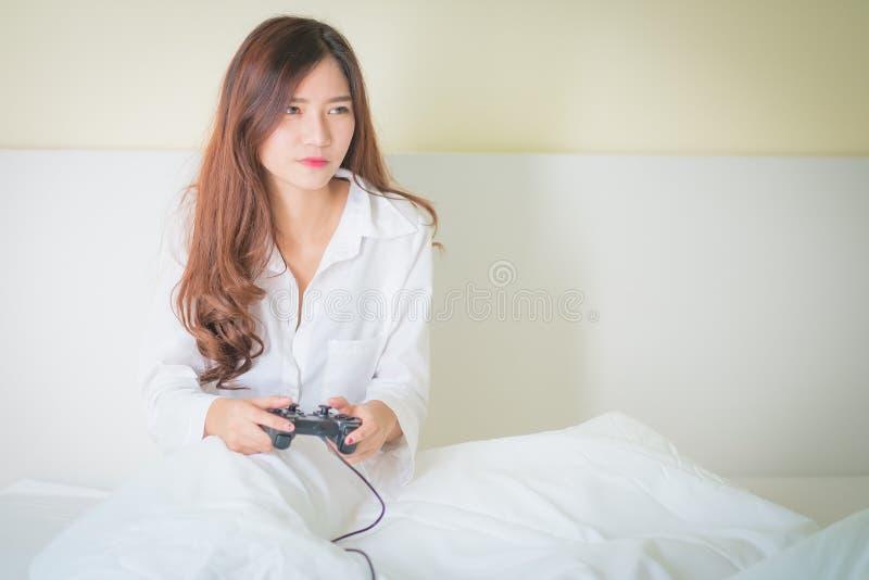 Portret van leuke meisje het spelen videospelletjes terwijl zij liggend o is royalty-vrije stock afbeelding