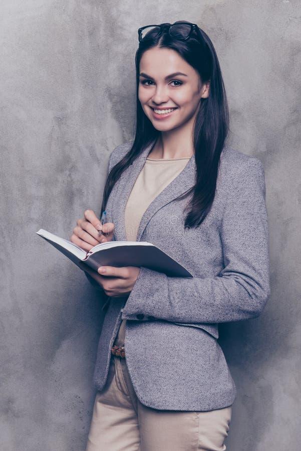 Portret van leuke mooie bedrijfsvrouwentribunes op een grijze backgrou stock foto's