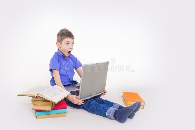 Portret van leuke schooljongenzitting met boeken en het typen op laptop toetsenbord royalty-vrije stock foto's