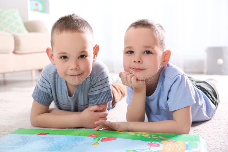 Portret van leuke tweelingbroers met boek op vloer stock foto's