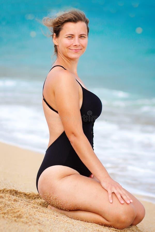 Portret van leuke vrouw in zwempak op strand Mooi jong meisje op zandig strand tegen blauwe zeewaterachtergrond royalty-vrije stock foto