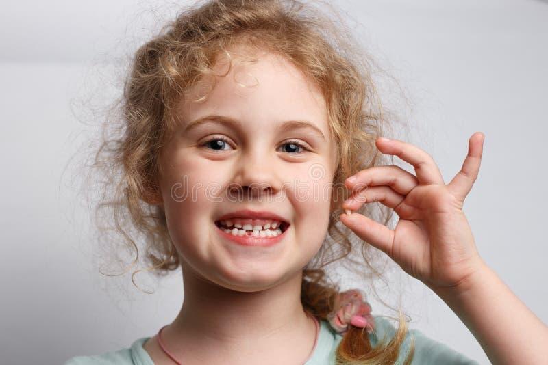 Portret van leuke zes jaar meisjes die haar eerste melktand verliezen stock fotografie