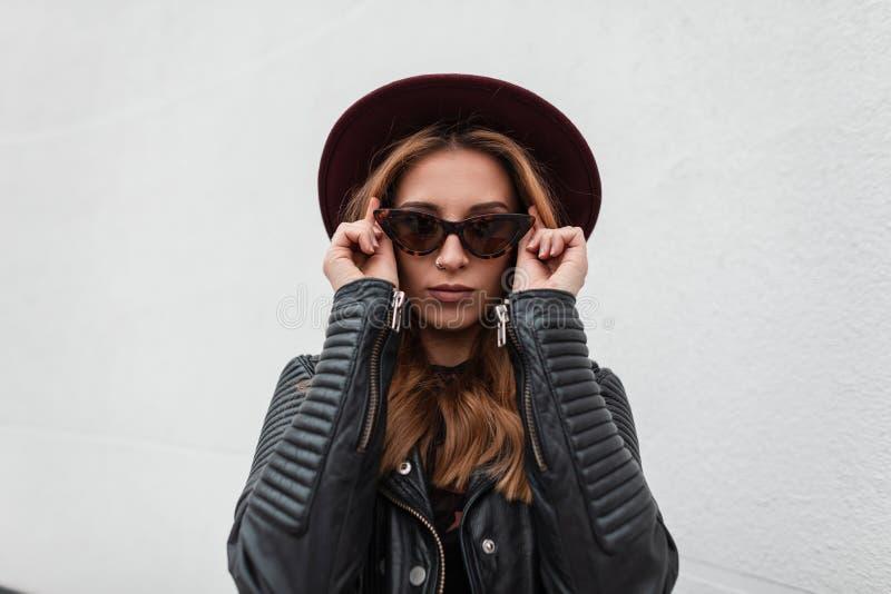 Portret van luxueuze roodharige hipster jonge vrouw in donkere modieuze zonnebril in purpere hoed in zwart modieus leerjasje stock afbeelding