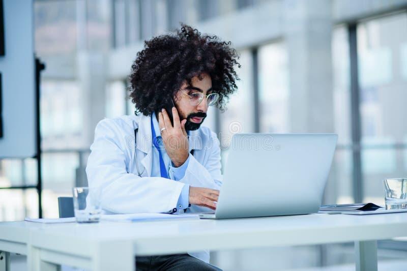 Portret van mannelijke arts die in het ziekenhuis zit en een laptop en smartphone gebruikt royalty-vrije stock afbeeldingen