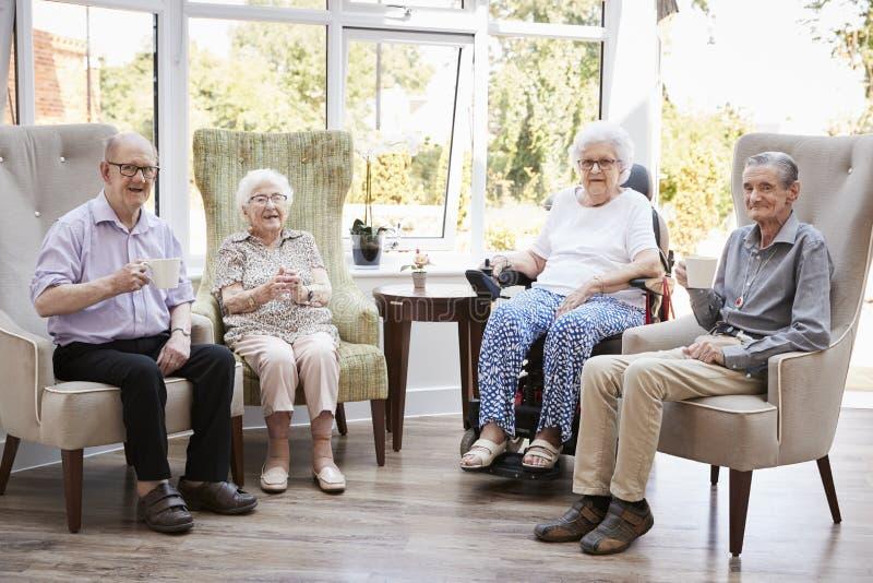 Portret van Mannelijke en Vrouwelijke Ingezetenen die als Voorzitter in Zitkamer van Pensioneringshuis zitten stock afbeelding