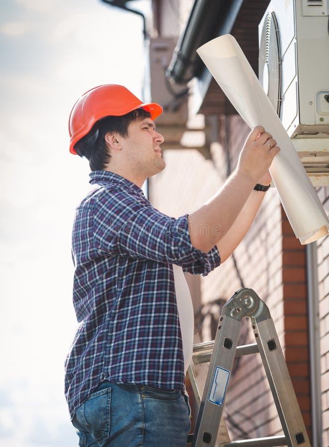 Portret van mannelijke ingenieur die blauwdrukken van het systeem van de huisairconditioning kijken stock foto's