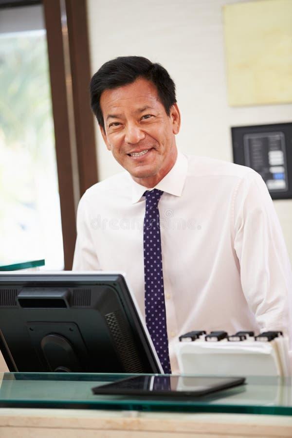 Portret van Mannelijke Receptionnist At Hotel Front Desk royalty-vrije stock fotografie