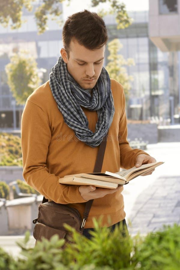 Portret van mannelijke student met boeken in openlucht stock fotografie