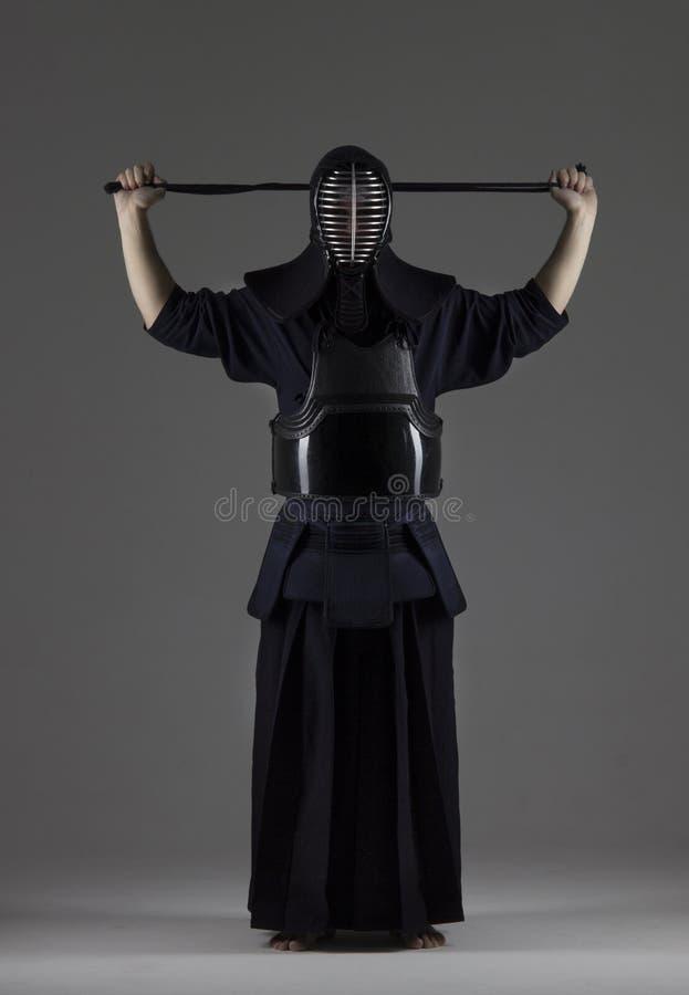 Portret van mannetje in het pantser die van traditiekendo zijn helm zetten en voor de strijd voorbereidingen treffen stock foto's