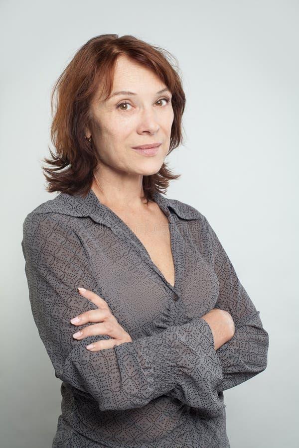 Portret van medio volwassen vrouw met gekruiste wapens royalty-vrije stock afbeelding