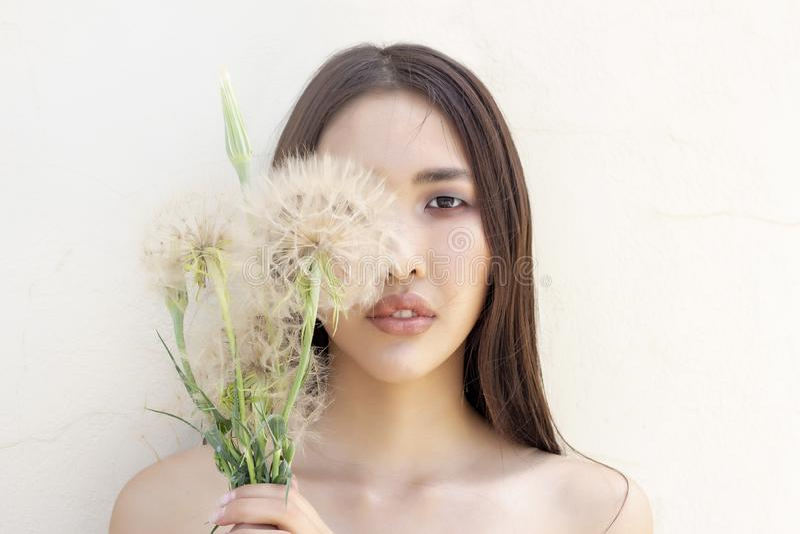Portret van meisje van Aziatische verschijning één oog is behandeld met een paardebloem Concept stock afbeelding