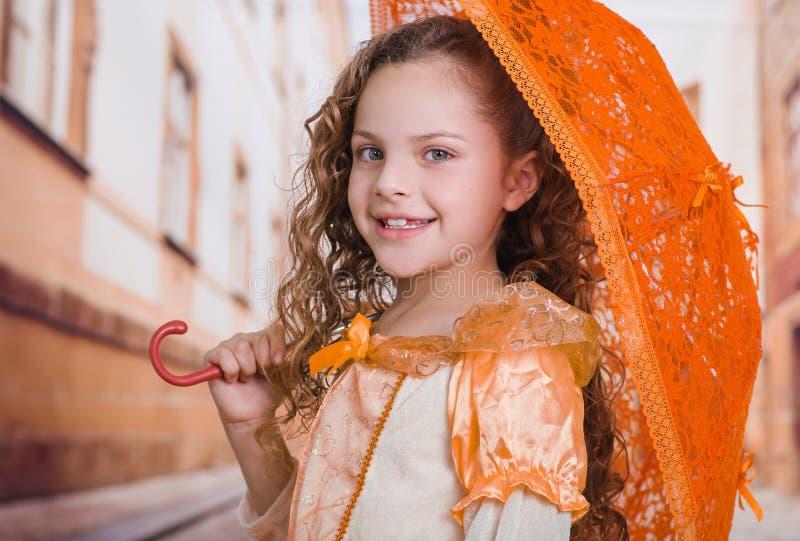 Portret van meisje die een mooi koloniaal kostuum dragen en een oranje paraplu op een vage achtergrond houden stock afbeelding