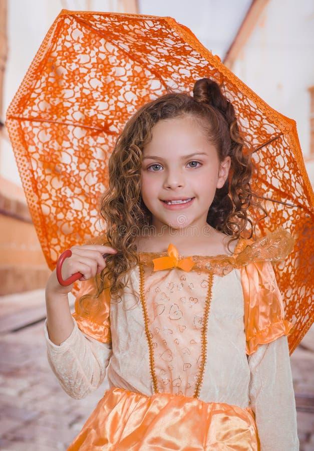 Portret van meisje die een mooi koloniaal kostuum dragen en een oranje paraplu op een vage achtergrond houden stock foto