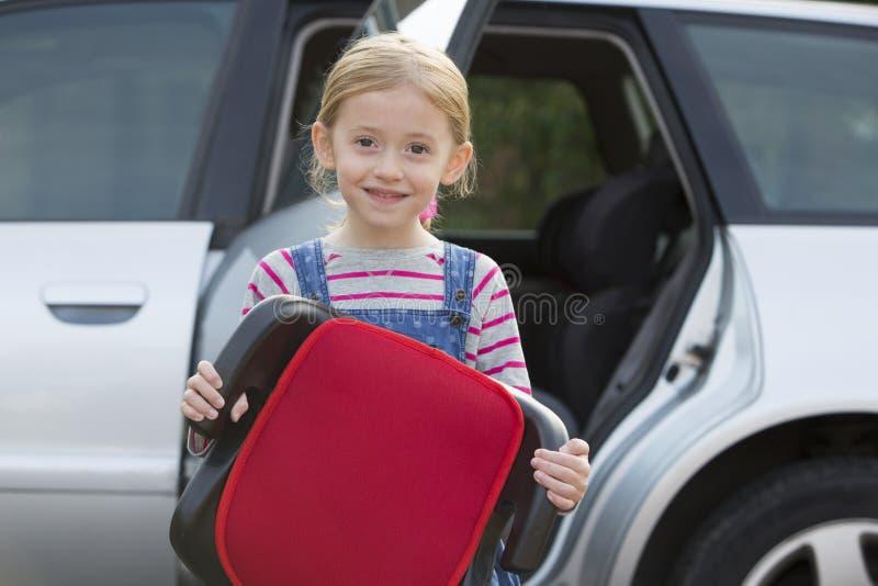 Portret van Meisjesholding Hulpseat die zich naast Auto bevinden stock afbeeldingen