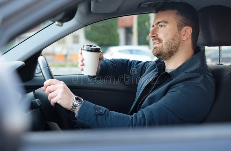 Portret van mens het drinken koffie terwijl het drijven van auto royalty-vrije stock fotografie