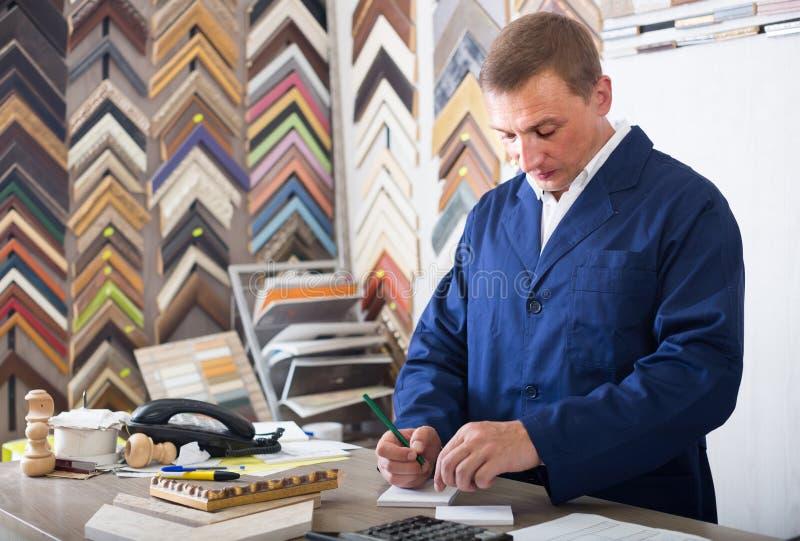 Portret van mensenverkoper het werken met omlijstingen in atelier stock afbeeldingen