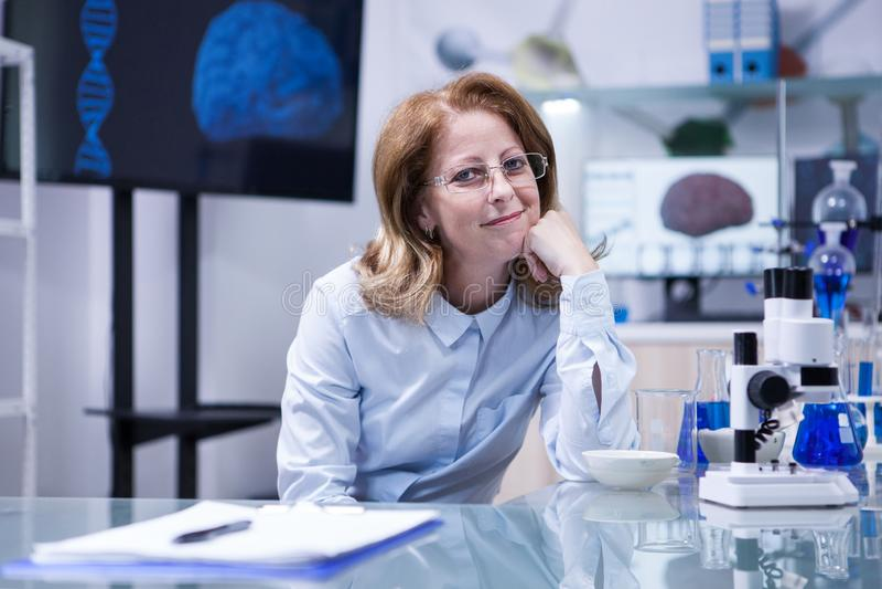 Portret van middenleeftijdswetenschapper die over haar carrière op haar kantoor in een het ziekenhuislaboratorium denken stock fotografie
