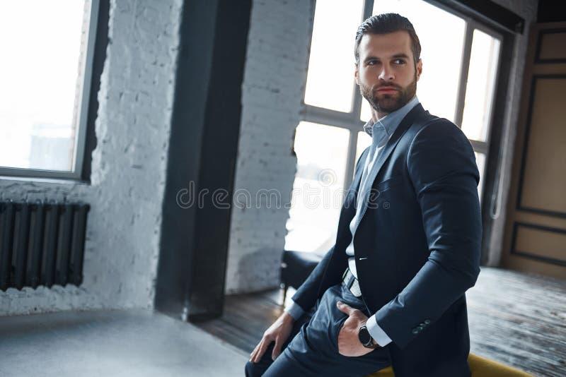 Portret van modieuze en modieuze jonge zakenman in een kostuum dat ernstig opzij eruit ziet en over het werk denkt royalty-vrije stock foto's