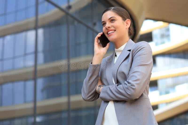 Portret van modieuze glimlachende bedrijfsvrouw die in modieuze kleren mobiele telefoon uitnodigen dichtbij bureau royalty-vrije stock afbeelding