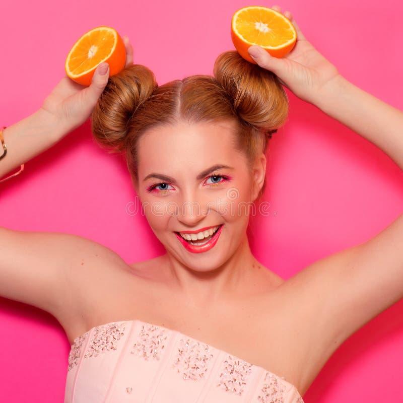 Portret van modieuze jonge blondevrouw met sinaasappelen royalty-vrije stock afbeelding