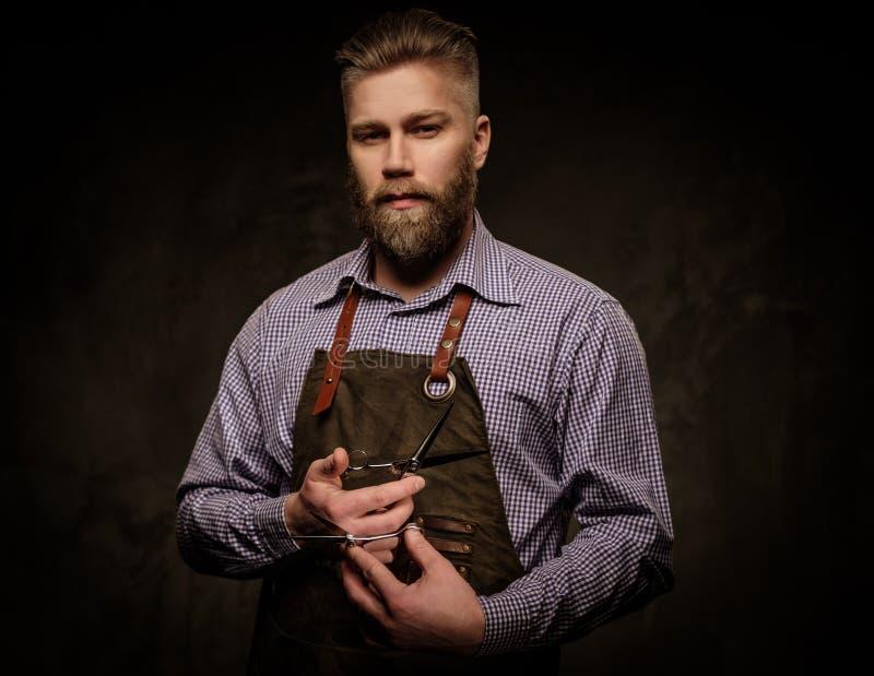Portret van modieuze kapper met baard en professionele hulpmiddelen op een donkere achtergrond stock foto