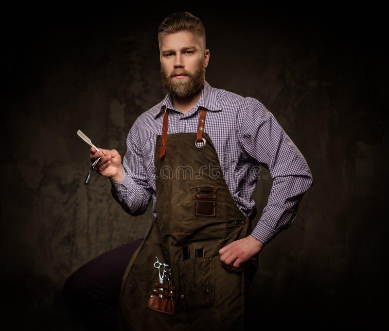Portret van modieuze kapper met baard en professionele hulpmiddelen op een donkere achtergrond stock afbeeldingen