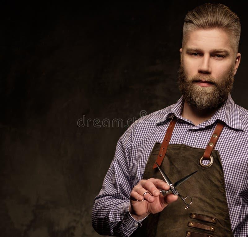 Portret van modieuze kapper met baard en professionele hulpmiddelen op een donkere achtergrond royalty-vrije stock foto's