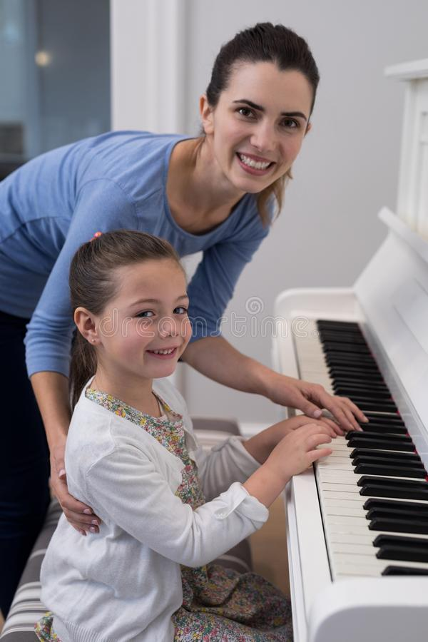 Portret van moeder bijwonende dochter in het spelen piano royalty-vrije stock fotografie
