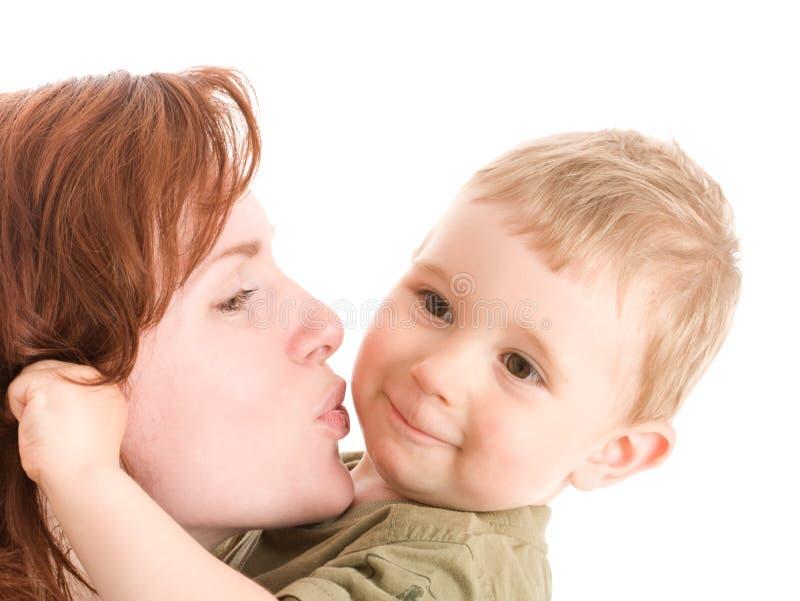 Portret van moeder die haar zoon kust stock afbeelding