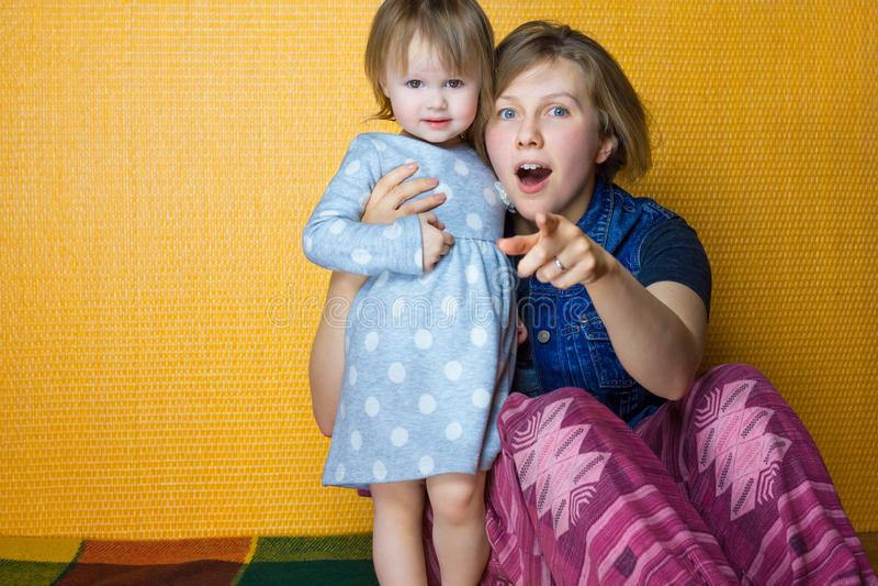 Portret van moeder die peuterdochter koesteren vrij, kijkt het verbaasde meisje aan camera vrouw, persoonspunt bij verrassing lan stock afbeelding