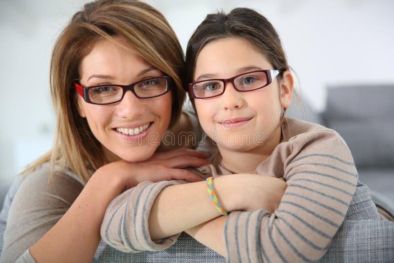 Portret van moeder en dochterzitting op bank stock foto