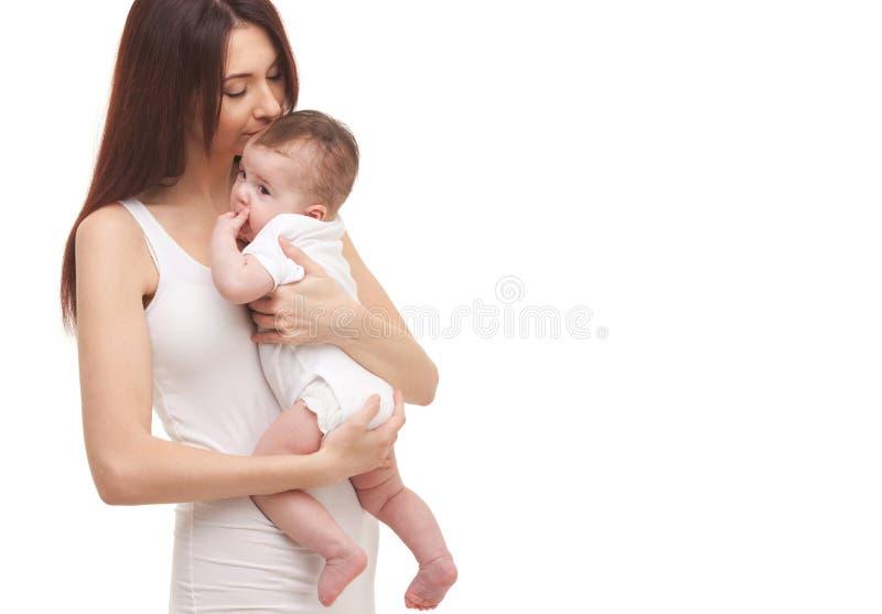 Portret van moeder en haar weinig kind in wit Gelukkig familieconcept Moeder die leuke die baby houden op witte achtergrond wordt royalty-vrije stock fotografie