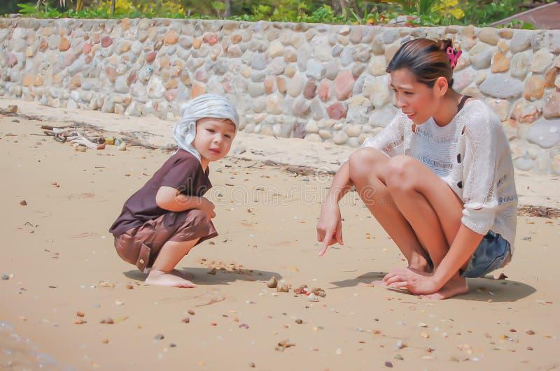 Portret van moeder en zoons het spelen met zand door het overzees stock afbeelding