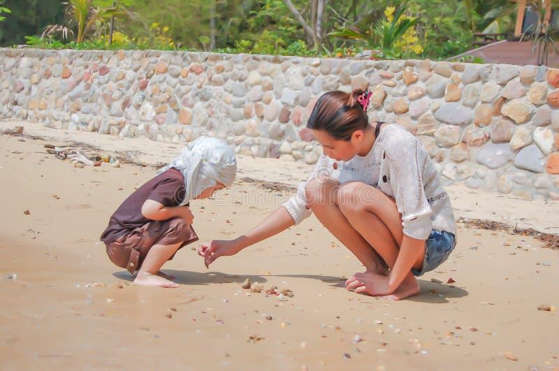 Portret van moeder en zoons het spelen met zand door het overzees stock fotografie
