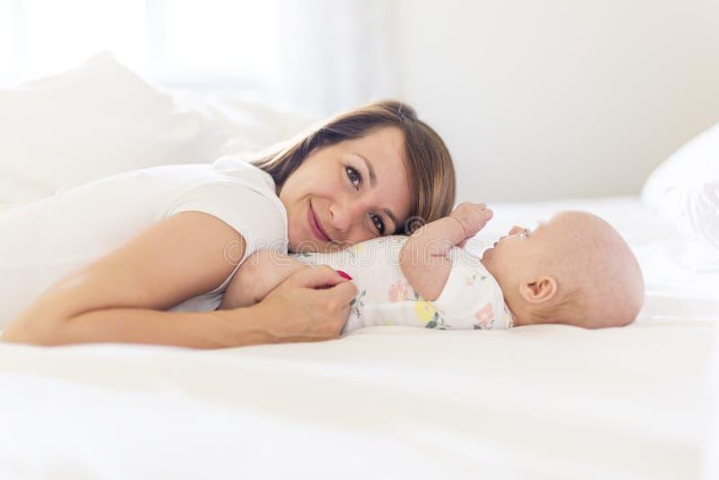 Portret van moeder met haar 3 maand oude baby in slaapkamer stock fotografie