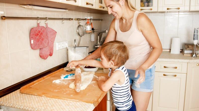 Portret van moeder met 3 jaar het bakselkoekjes van de peuterzoon op keuken bij ochtend Familiebaksel en thuis het koken royalty-vrije stock foto