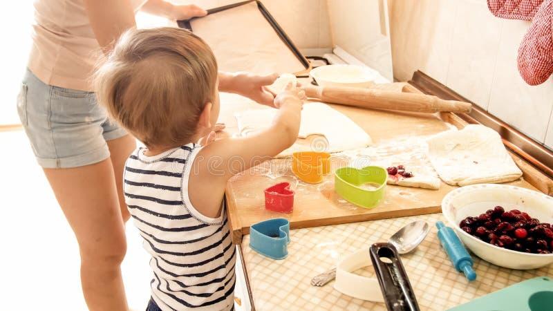 Portret van moeder met 3 jaar het bakselkoekjes van de peuterzoon op keuken bij ochtend Familiebaksel en thuis het koken royalty-vrije stock afbeelding