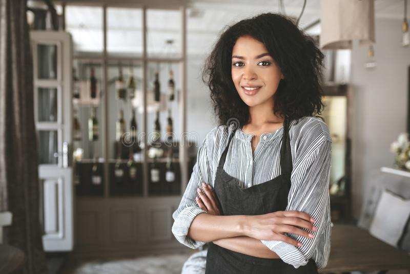 Portret van mooi Afrikaans Amerikaans meisje die overhemd en schort in restaurant dragen stock afbeeldingen