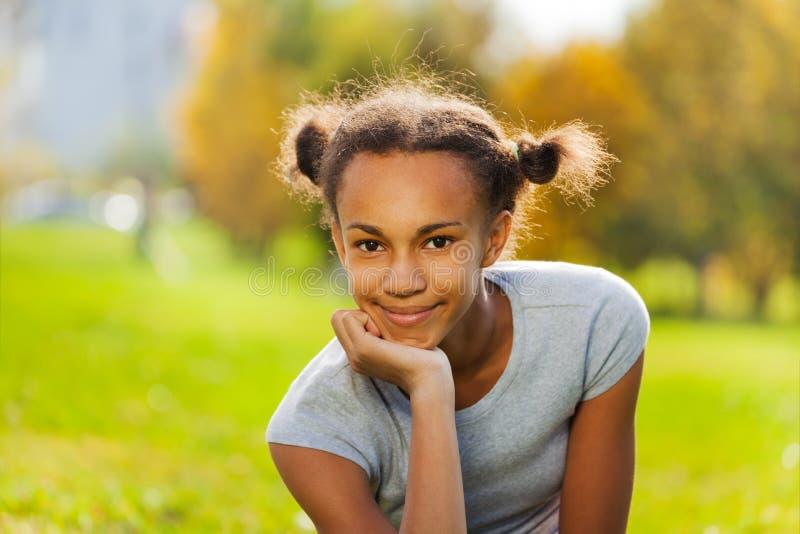 Portret van mooi Afrikaans meisje op groen gras royalty-vrije stock afbeelding