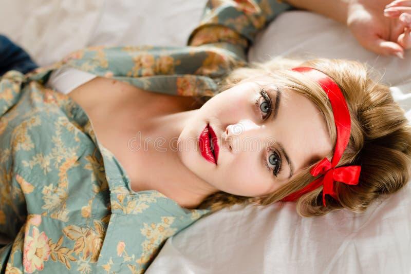 Portret van mooi blond sexy pinupmeisje in bloemenoverhemd die pret ontspannen hebben die op terug in wit bed liggen stock fotografie
