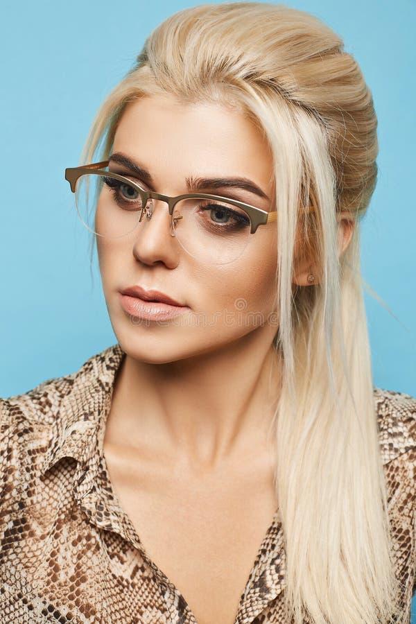 Portret van mooi blonde modelmeisje met blauwe ogen en perfecte huid in modieuze glazen en in de modieuze blouse royalty-vrije stock foto