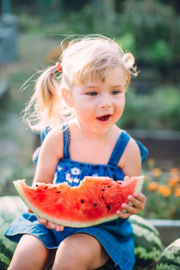 Portret van mooi blondemeisje die met twee paardestaarten watermeloen eten royalty-vrije stock afbeelding