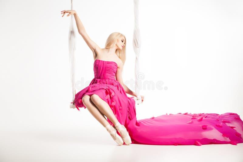 Portret van mooi blondemeisje op schommeling in heldere roze kleding stock foto